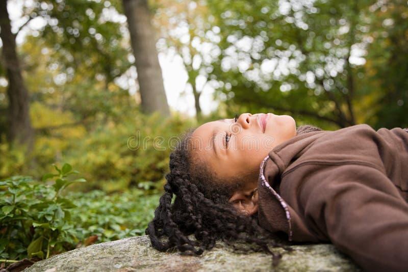 Flicka i en skog arkivbild