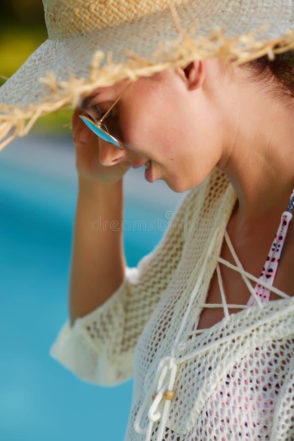 Flicka i en solhatt därefter pölen royaltyfri foto
