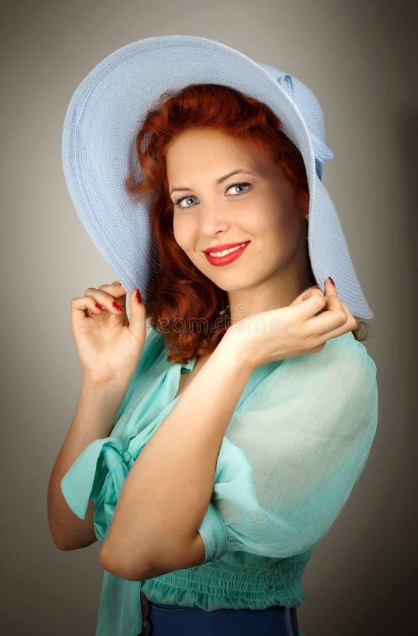 Flicka i en stor blå hatt i studion royaltyfri foto