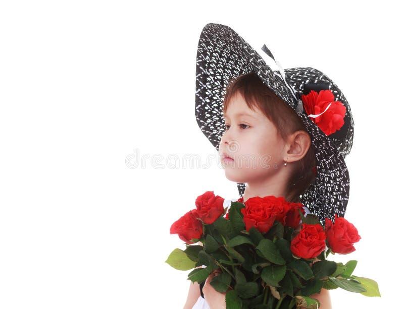 Flicka i en stor bukett för hatt av röda rosor royaltyfri fotografi