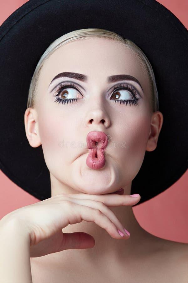 Flicka i en svart hatt med en grafisk kvalitets- makeup royaltyfria bilder