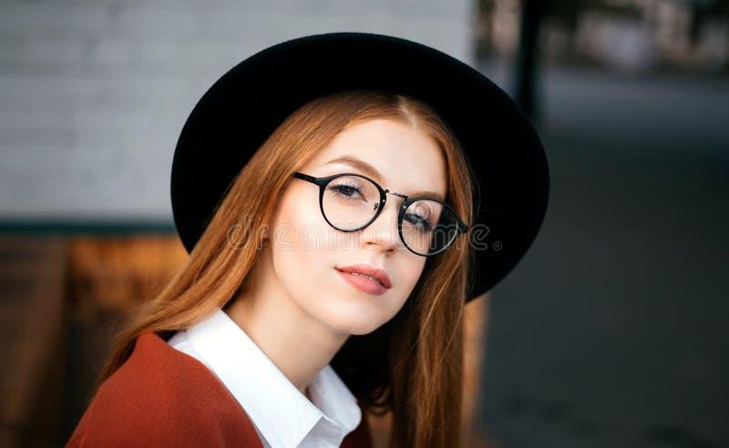 Flicka i en svart hatt och exponeringsglas royaltyfria foton