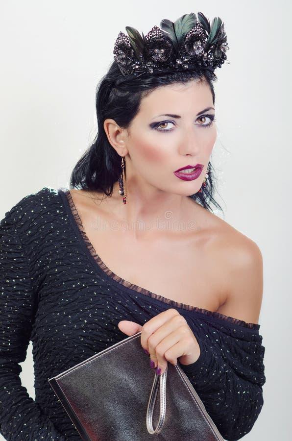 Flicka i en svart klänning och med en påse arkivfoto