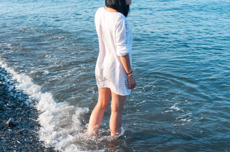 Flicka i en vit kl?nning som promenerar kusten fotografering för bildbyråer