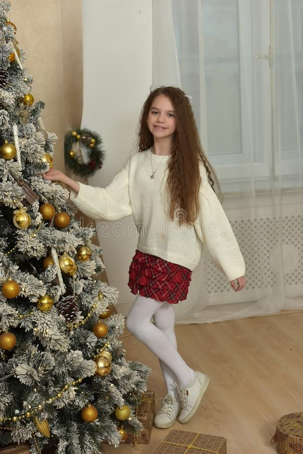 flicka i en vit tröja nära julgranen arkivbilder
