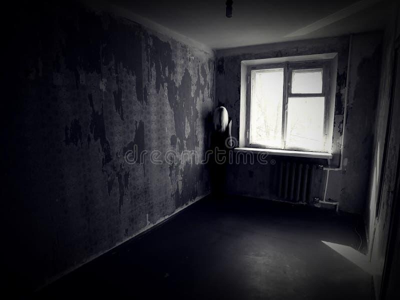 Flicka i ett övergett kusligt rum arkivfoton