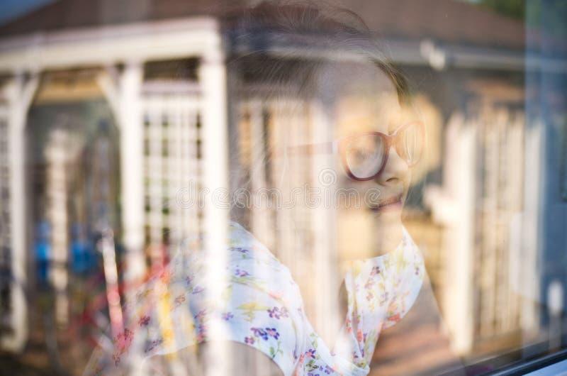 Flicka i ett fönster med trädgårds- refelctions arkivbilder