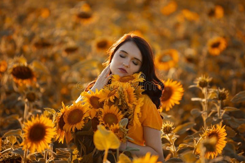 Flicka i ett f?lt av solrosor arkivfoton