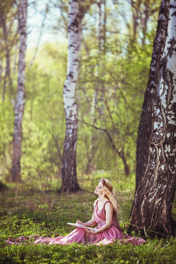 Flicka i ett felikt klänningsammanträde under ett träd royaltyfri foto