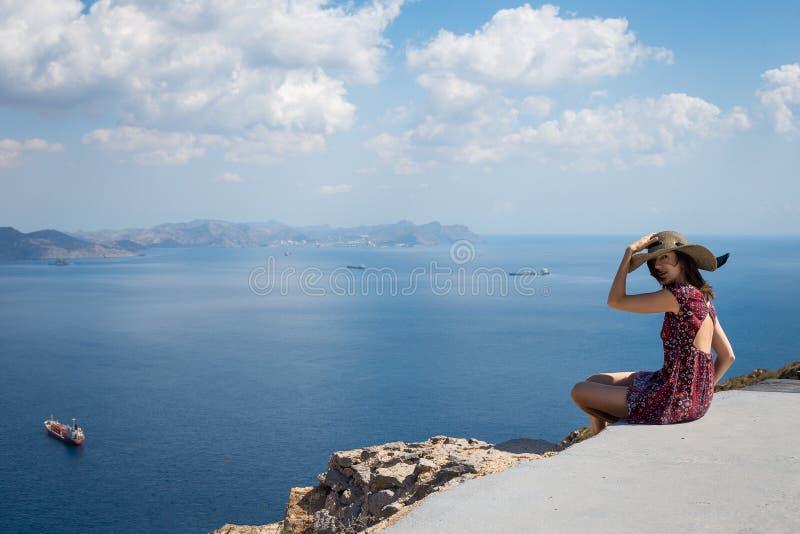 Flicka i ett hattsammanträde på kanten av berget som vänder mot havet royaltyfria foton