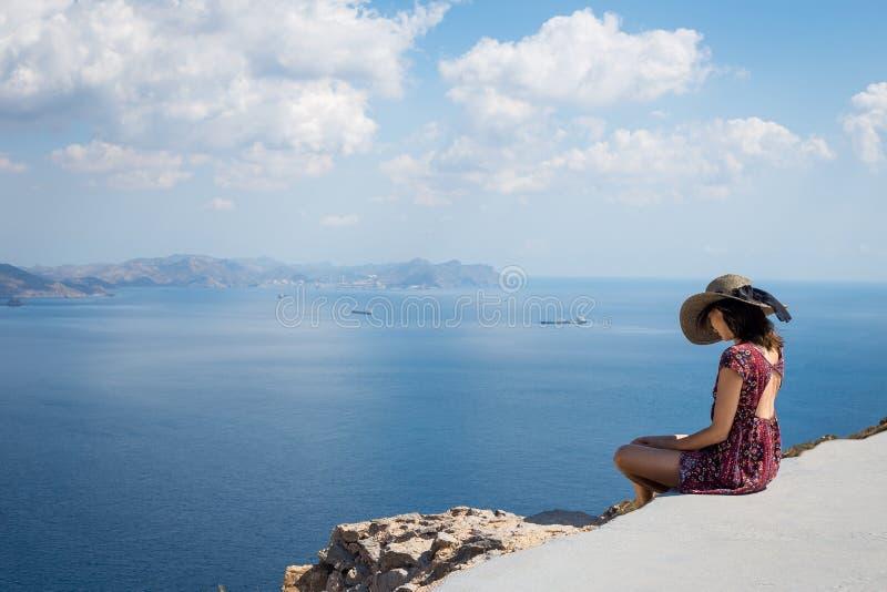 Flicka i ett hattsammanträde på kanten av berget som vänder mot havet royaltyfri foto