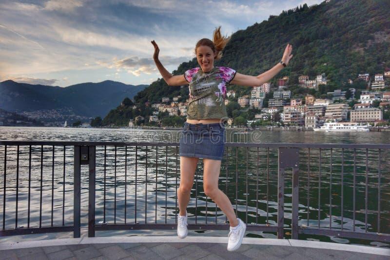 Flicka i ett hopp I bakgrunden är staden och sjön Como royaltyfri bild