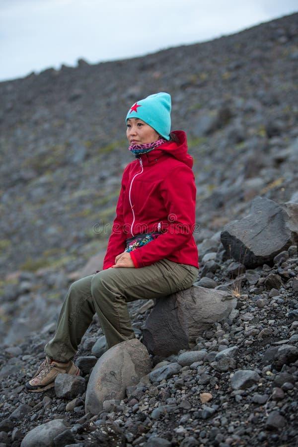 Flicka i ett rött omslag som sitter på en sten på bakgrunden av en stenig lutning royaltyfri bild