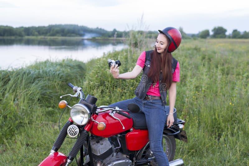 Flicka i ett retro hjälmsammanträde på en tappningmotorcykel med en kamera royaltyfria foton