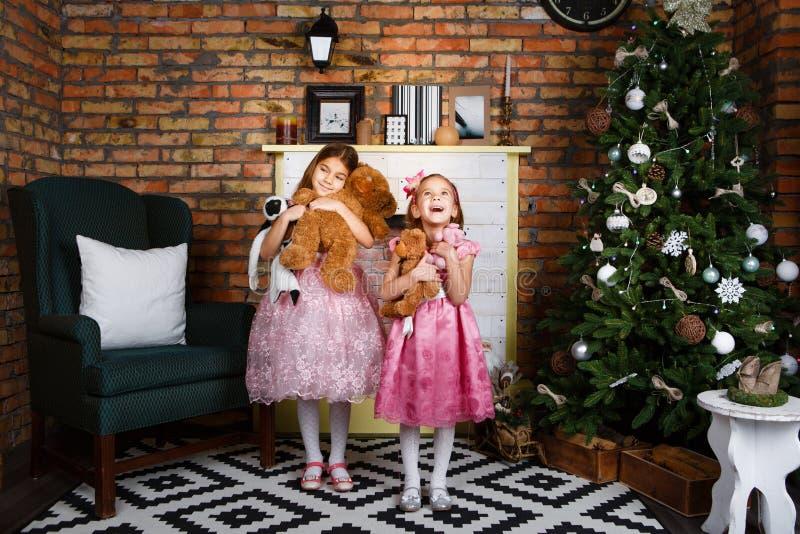 Flicka i ett storartat klänninganseende på julgranen royaltyfria foton