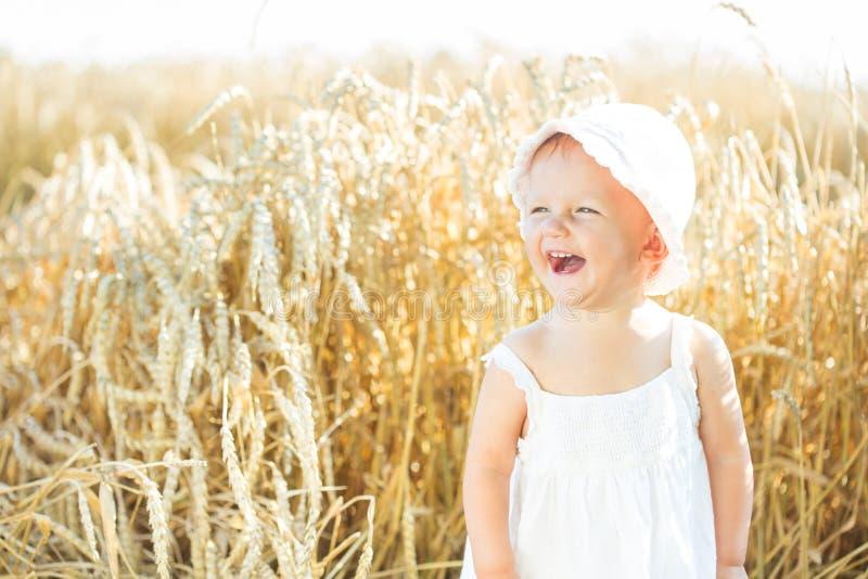 Flicka i ett vetefält arkivbild