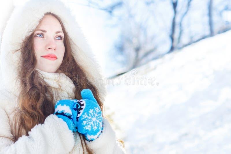 Flicka i ett vitt pälslag med blåa ögon mot en bakgrund av arkivbild