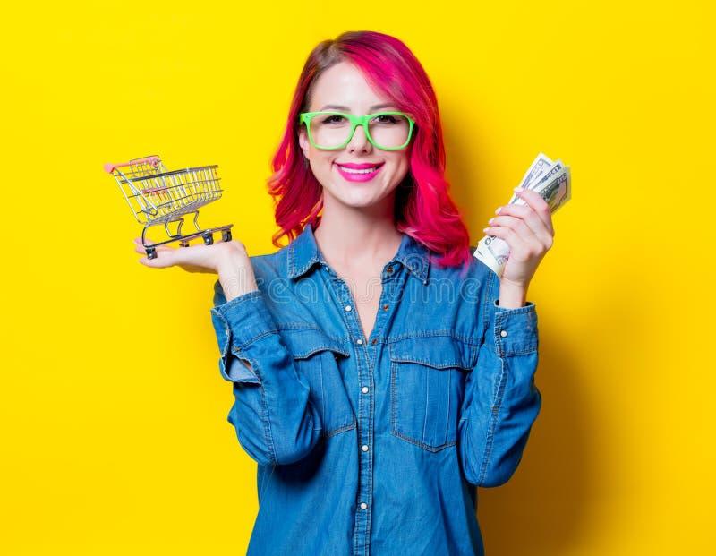 Flicka i exponeringsglas som rymmer shoppingvagnen och pengar arkivfoton