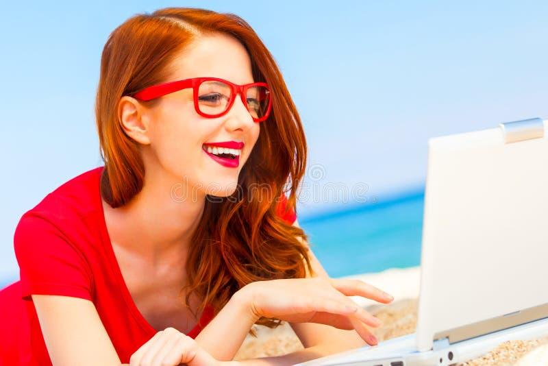 Flicka i exponeringsglasen med anteckningsboken på stranden royaltyfri foto