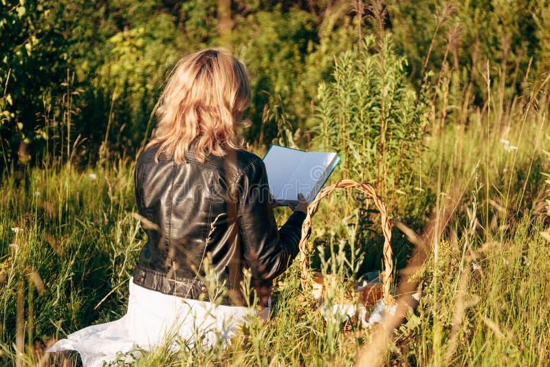 Flicka i fält som läser en bok Flickasammantr?det p? ett gr?s som l?ser en bok arkivfoton