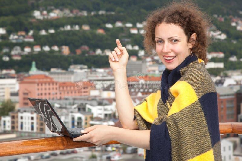 Flicka i filt med bärbar dator på däck