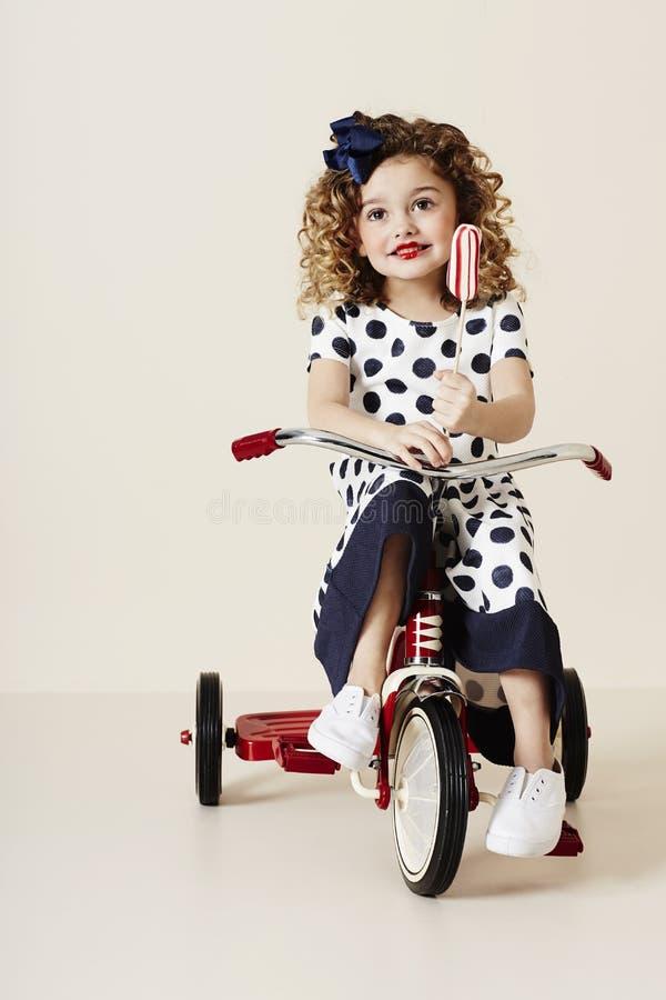 Flicka i fläckar på trehjulingen royaltyfria bilder