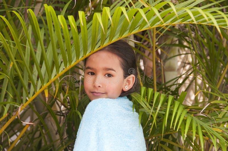 Flicka i gömma i handflatan-tree arkivfoton