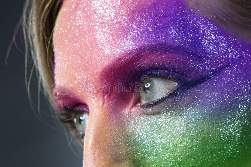 Flicka i gnistrande färgad makeupmaskering arkivbilder
