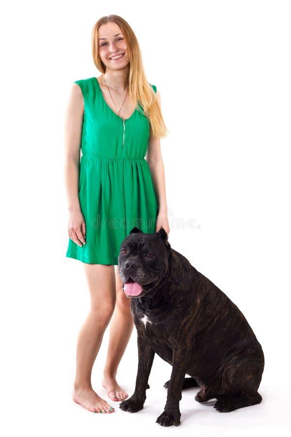 Flicka i grönt klänninganseende bredvid en stor hund Cane Corso royaltyfria bilder