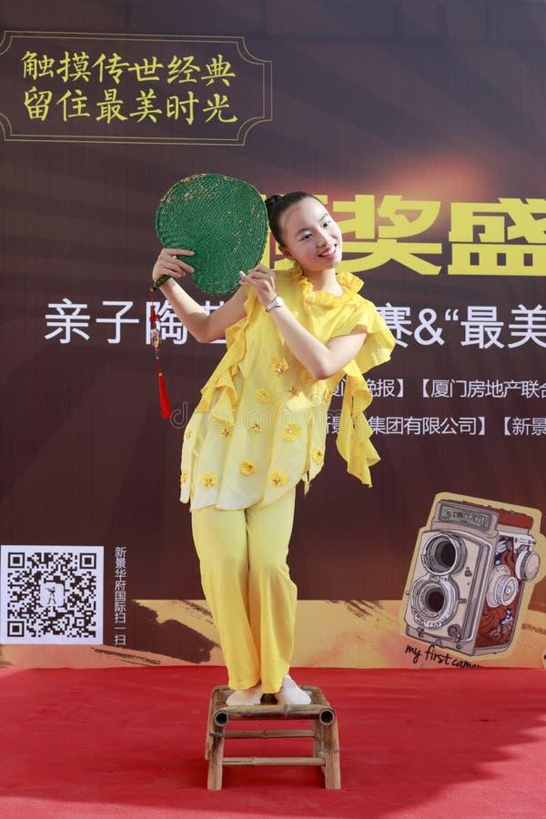 Flicka i gul kapacitetsfandans på liten bambustol royaltyfri foto