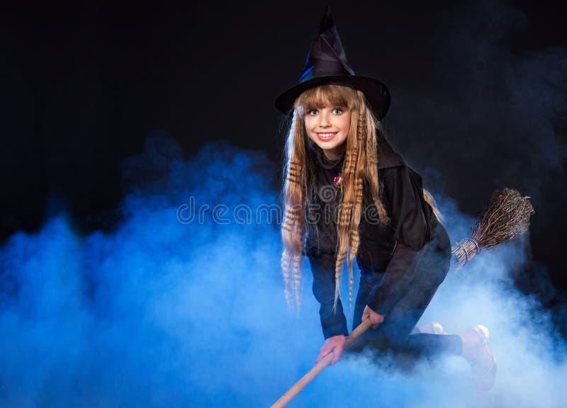 Flicka i häxas hattflyg på kvastskaften. fotografering för bildbyråer