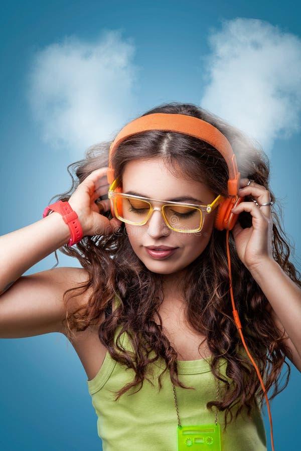 Flicka i hörlurar med stängda ögon som lyssnar till musik arkivbilder