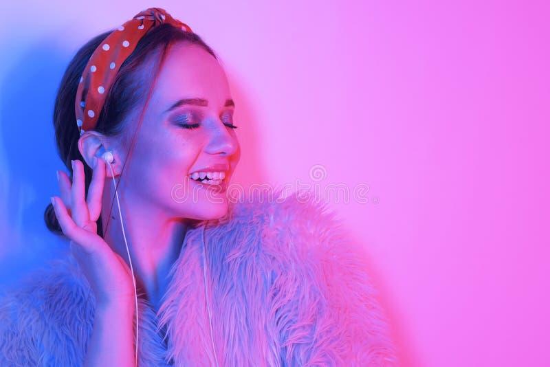 Flicka i h?rlurar som lyssnar till musik De flickaleendena och skratten Modestående av den unga eleganta flickan i ett rosa lag o royaltyfri foto