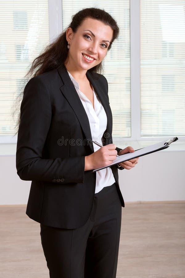 Flicka i handstil för affärsdräkt i en dokumentmapp arkivbilder