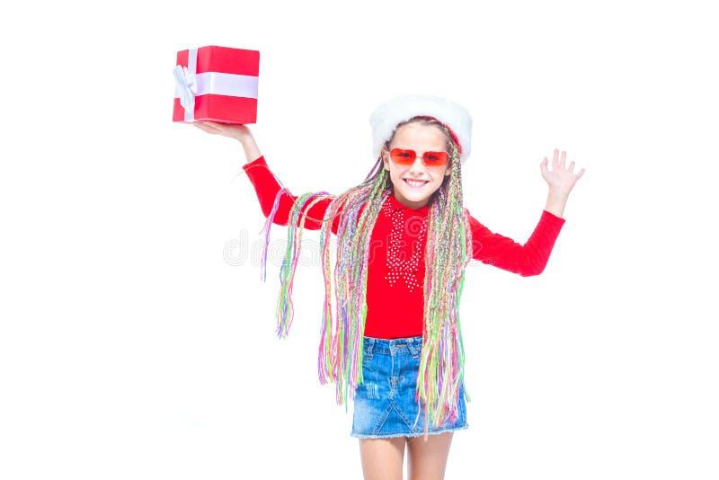 Flicka i hatt för santa ` s Ståenden av den lilla gulliga flickainnehavasken av julklapp, den lilla flickan kramar hennes gåva me royaltyfria bilder