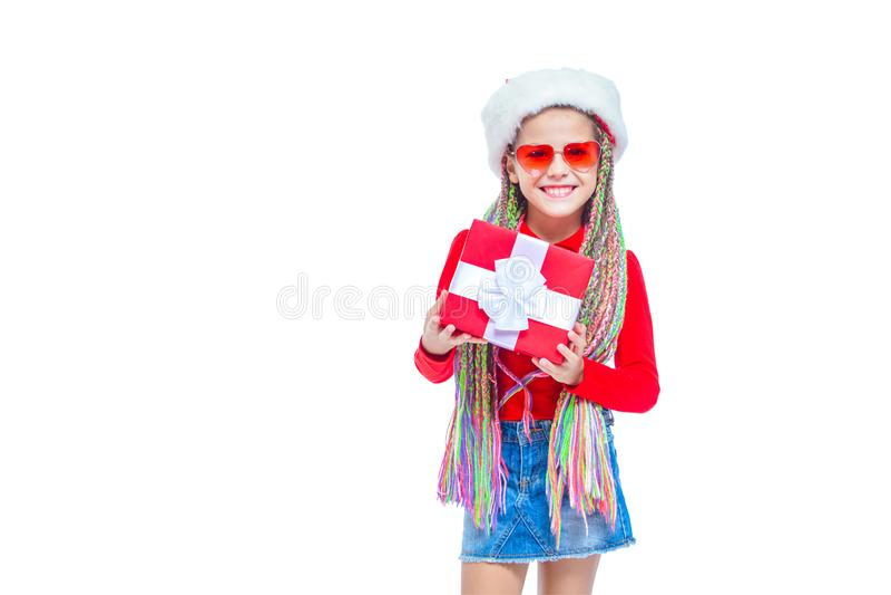 Flicka i hatt för santa ` s Ståenden av den lilla gulliga flickainnehavasken av julklapp, den lilla flickan kramar hennes gåva me arkivbild