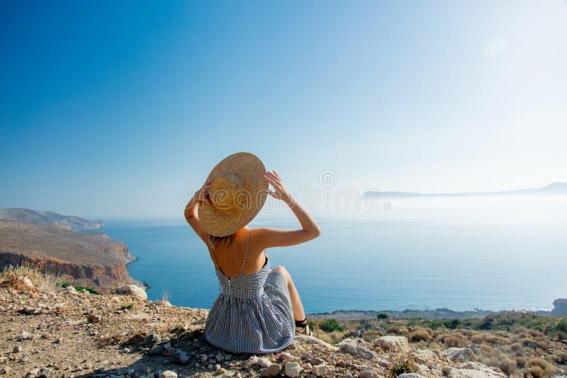 Flicka i hatt och klänning med havskustlinjen royaltyfri fotografi