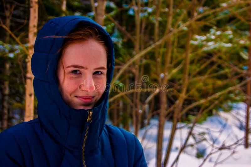 Flicka i huven i vinter arkivbild