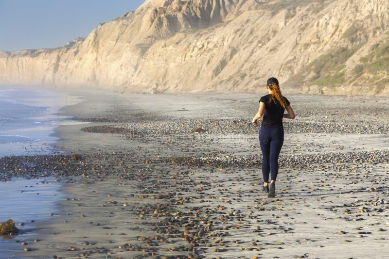 Flicka i idrotts- kläder som joggar på Torrey Pines State Beach San Diego California arkivbilder