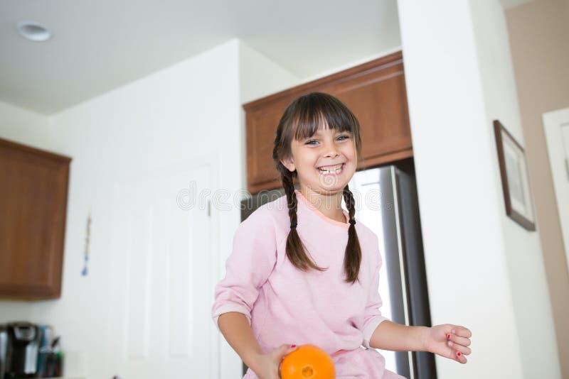 Flicka i kök med ett stort leende som rymmer en apelsin royaltyfri fotografi