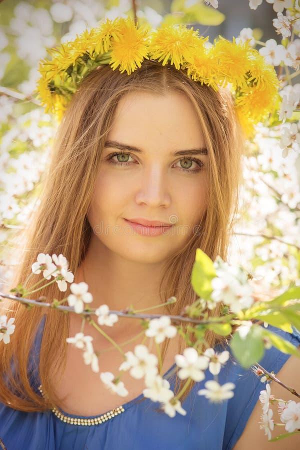 Flicka i körsbärsröda blommor arkivbilder