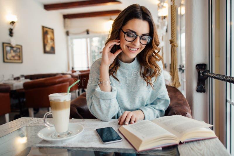 Flicka i kafé som läser den roliga boken royaltyfri foto