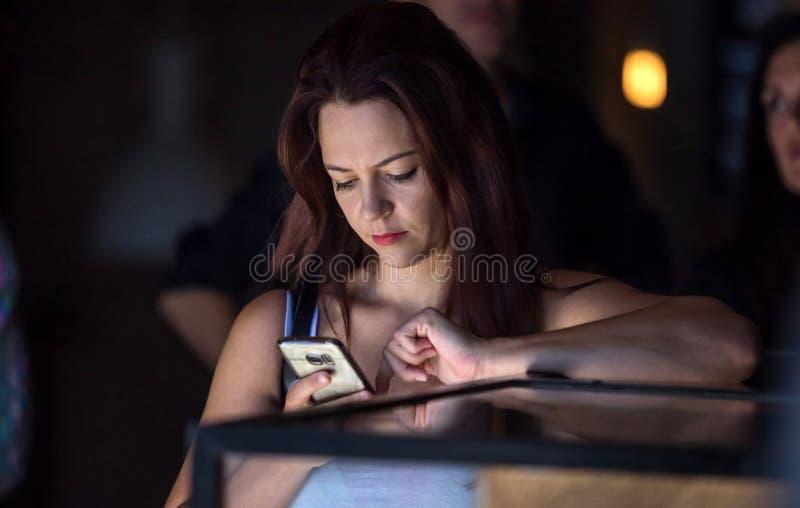 Flicka i kafét som ser mobiltelefonen fotografering för bildbyråer