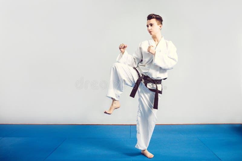 flicka i karatedräktkimono i studio på grå bakgrund Det kvinnliga barnet visar judo- eller karatestans i den vita likformign med  arkivfoton