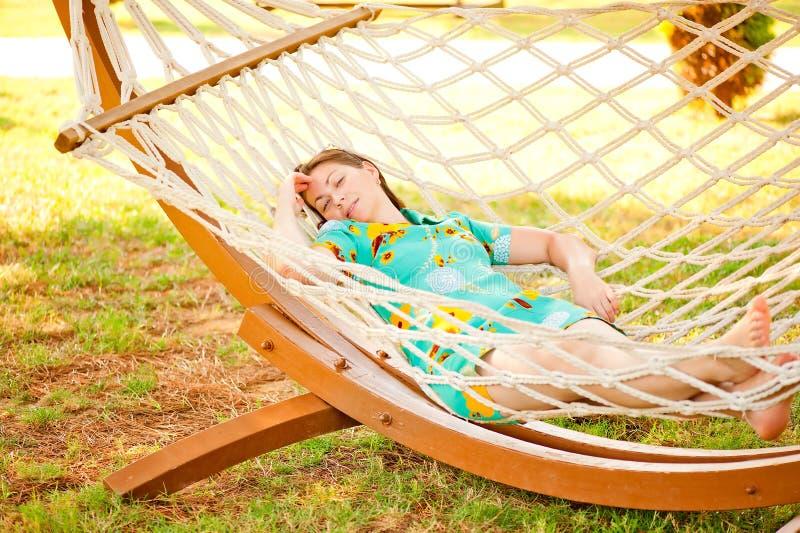 Flicka i klänning som vilar i en hängmatta fotografering för bildbyråer
