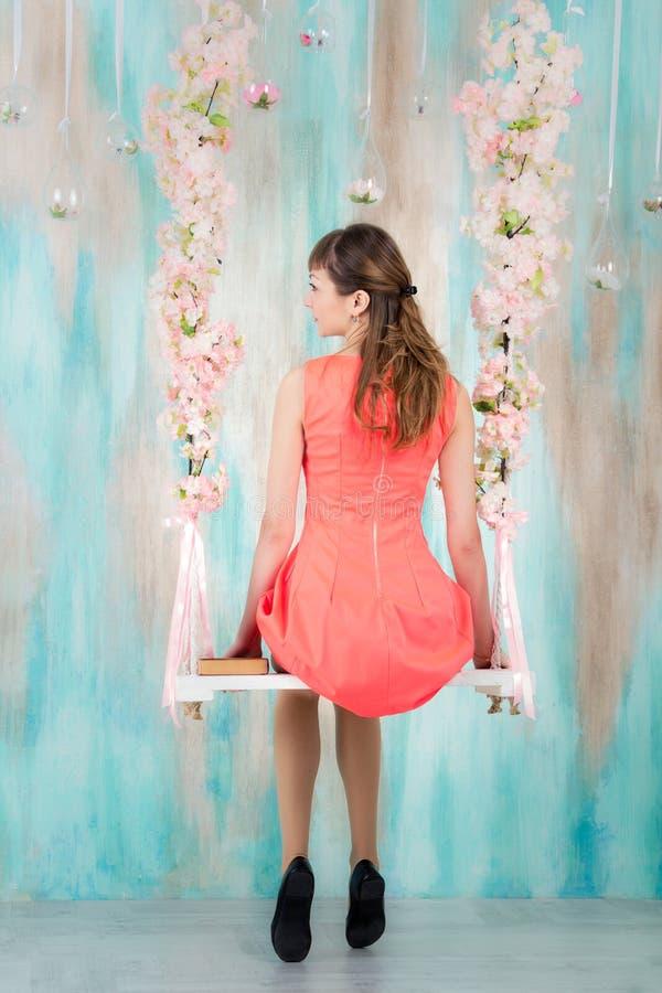 Flicka i klänningsammanträde på gunga arkivbilder