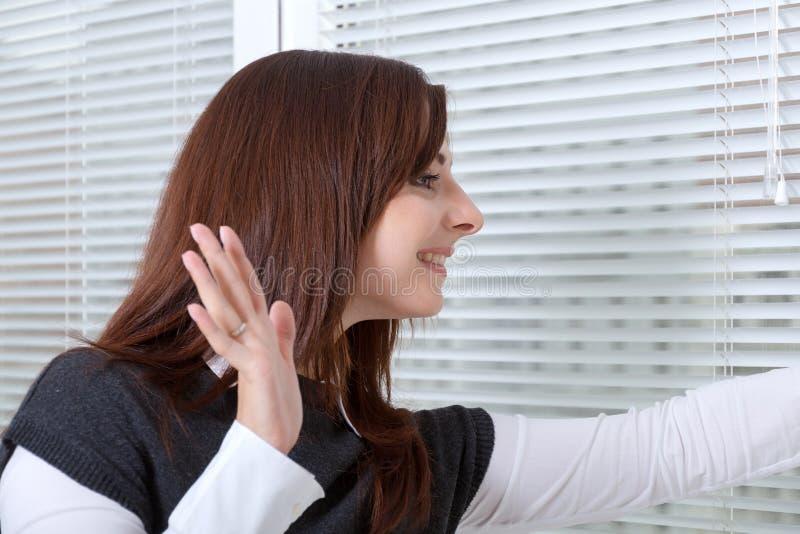 Flicka i kontoret som vinkar hennes hand till någon i gatan royaltyfria foton