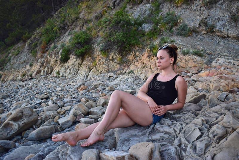 Flicka i kortslutningar och enskjorta med exponeringsglas som vilar på en stenig kust royaltyfri bild