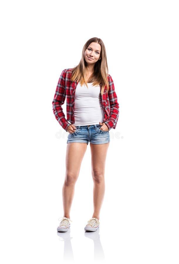 Flicka i kortslutningar och skjorta, hand i fack som isoleras royaltyfri foto