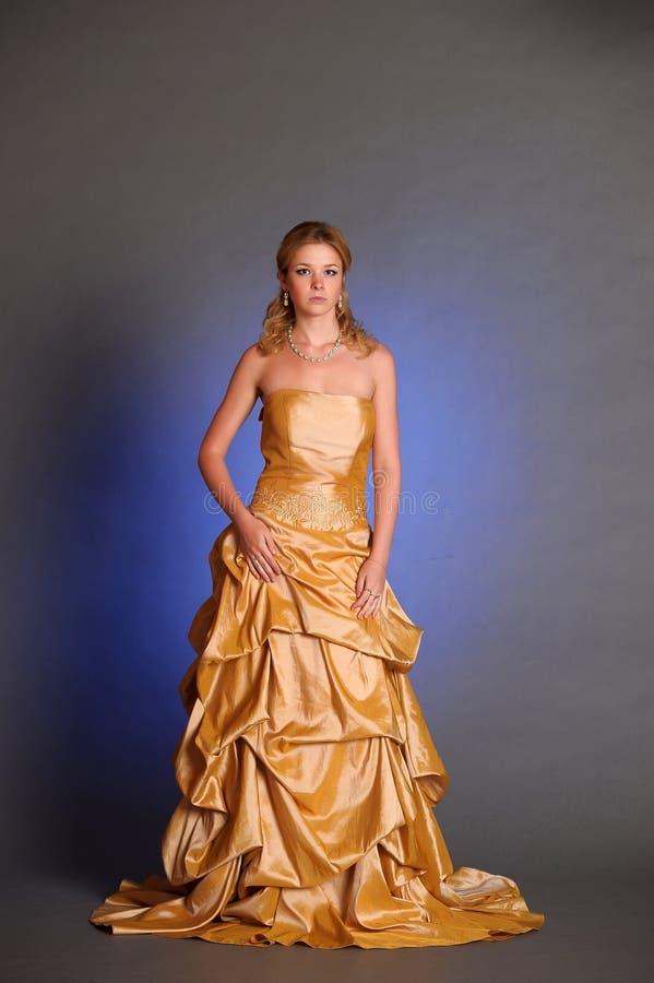 Flicka i lång klänning för gul afton arkivfoton